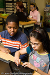 Public Middle School Grade 6 boy and girl working together at laptop computer vertical