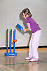 Young girl playing a game of indoor cricket in the sports hall of her local leisure centre,