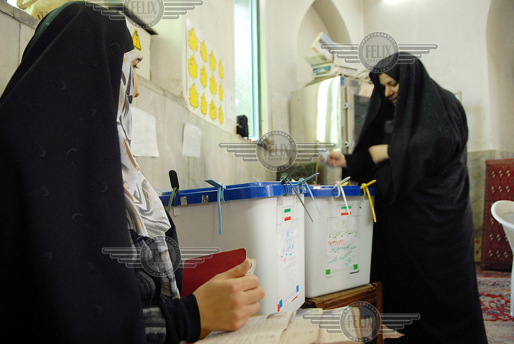 An election official at Ershad mosque looks on as a woman casts her vote in the 2009 presidential election.