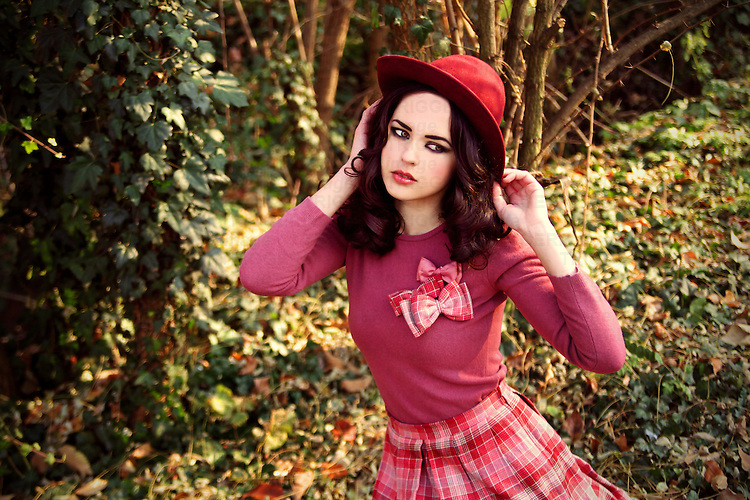 A prety brunette in a hat and pink vintage clothing sitting in a park.