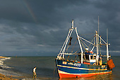 Hastings, East Sussex, England. Red and blue fishing boat Four Brothers coming to shore in the afternoon sun with fisherman waiting and a small rainbow in a steel sky.