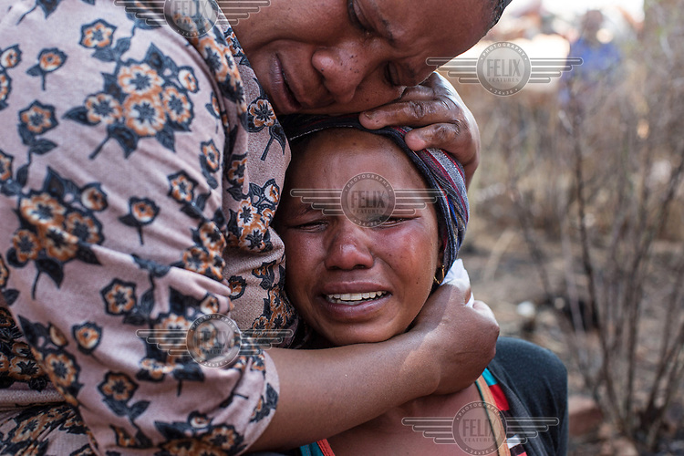 Nokulunga Mbangi cries after being told that her husband Isaac Mofali had been killed by the Red Ants. He was (allegedly) beaten to death with crowbars. She is comforted by her sister-in-law Sophie Mofali. The death was one of two that occured during a so-called 'demolition' operation to clear dwellings and evict squatters from land in Vlakfontein.  The Red Ants are a controversial private security company often hired to clear squatters from land and so-called 'hijacked' properties.