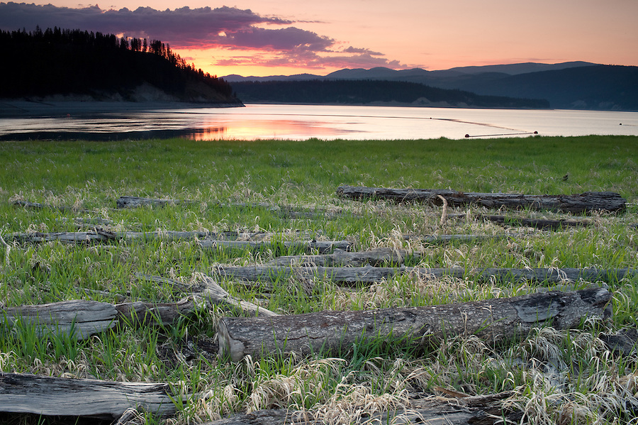 Old, dead logs decorate the foreground near the shore of Lake Coeur d'Alene in Northern Idaho at sunset.