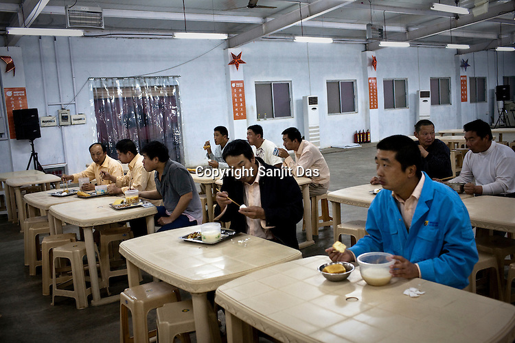 The dining hall of the Chinese colony of Adani Power plant in Mundra port industrial city of Gujarat, India. Indian power companies have handed out dozens of major contracts to Chinese firms since 2008. Adani Power Ltd have built elaborate Chinatowns to accommodate Chinese workers, complete with Chinese chefs, ping pong tables and Chinese television. Chinese companies now supply equipment for about 25% of the 80,000 megawatts in new capacity.