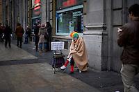 Un signore vestito da pagliaccio chiede l'elemosina nel centro di Madrid.