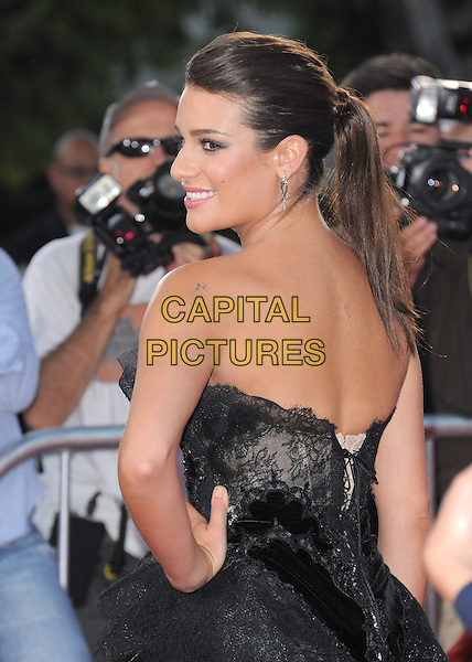 Lea Michele.attends The 20th Century Fox 'Glee 3D' Concert World Movie Premiere held at The Regency Village theatre in Westwood, California, USA, .August 6th 2011..half length ponytail profile side hand on hip dress smiling strapless black make-up beauty hair up  eyelashes tulle  silver earrings lace back over shoulder rear behind .CAP/RKE/DVS.©DVS/RockinExposures/Capital Pictures.