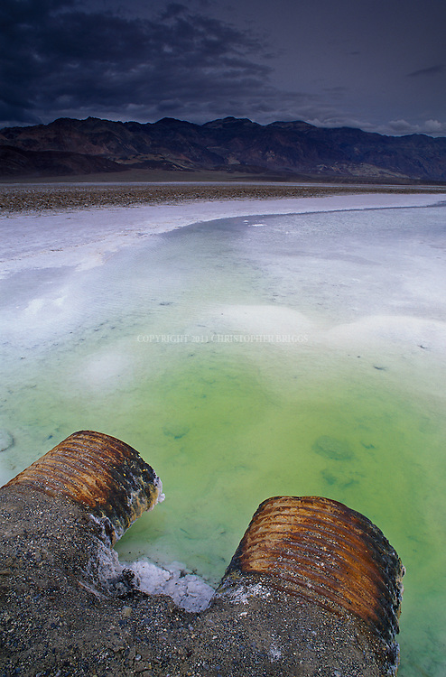Alkalai salt flats and algae pools created by the evaporation of spring rains on the valley floor. Black Mountains in the background. Death Valley National Monument Est. February 11, 1933. Est. as Death Valley National Park in 1994; 5,270 square miles (13,649 km2). Inyo County, CA.