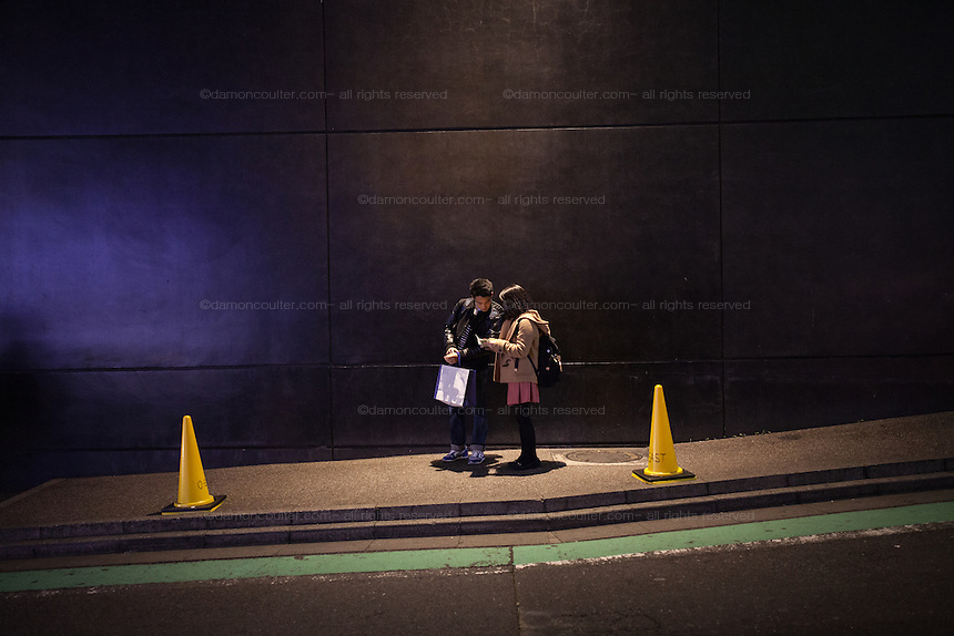 A young Japanese couple check tickets outside a music venue in Shibuya, Tokyo, Japan. Friday March 25th 2016