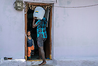 A local resident carries iJal water to his house in Ambedkar Nagar in Medak, Telangana, India.
