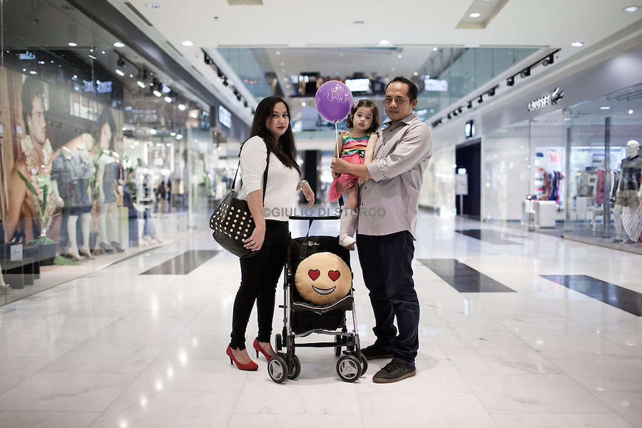JAKARTA, INDONESIA, MAY 2013:<br /> Denny, Rina and their Daughter Cira spending their Saturday afternoon at the Grand Indonesia Mall,<br /> Grand Indonesia mall, opened 4 years ago, is one of the main attraction in Jakarta for young people and middle class family, May 2013.<br /> © Giulio Di Sturco for Bloomberg Markets