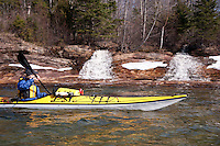 Lake Superior sea kayaker explores icy shoreline and waterfalls in spring on Michigan's Upper Peninsula.