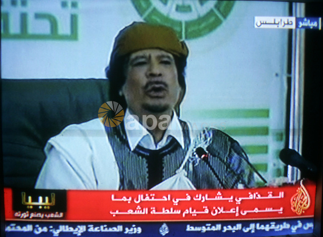 "A picture taken from Qatar Al Jazeera state television on March 02, 2011 shows Libyan leader Moammar Qadhafi addressing to the loyalists of his regime during a public rally in Tripoli, as rebels fought back his forces east of the capital. The Libyan leader was surrounded by dozens of supporters in a large ballroom for a ceremony to mark 34 years of ""people power"". Photo by Abed Rahim Khatib"