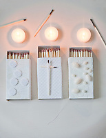 A trio of matchboxes have been decorated with pieces of wallpaper, beads, thread and felt