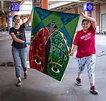 "Amy Kellenberger '15, left, and senior Naomi Maturino carry a mural celebrating DePaul's Black Student Union, Saturday, July 28, 2018, as they join other artists installing three new murals under the Fullerton ""L"" Station in Lincoln Park. The colorful montage of historical images highlighting the 50th anniversary of DePaul's Black Student Union also remembers the student protests of 1969 held on campus. Other murals installed in July included a caricature of DePaul basketball star George Mikan, a 1959 Naismith Memorial Basketball Hall of Fame inductee, and a mural celebrating the opening of DePaul's Loop Campus.<br /> <br /> The murals, part of a project started by Brother Mark Elder, C.M., an adjunct faculty member in DePaul's art, media and design program, is titled ""The Story of 'The Little School Under the 'L'', and will eventually feature 25 murals permanently installed on the massive concrete pillars that support the ""L"" station nearest the university's Lincoln Park Campus. (DePaul University/Jamie Moncrief)"