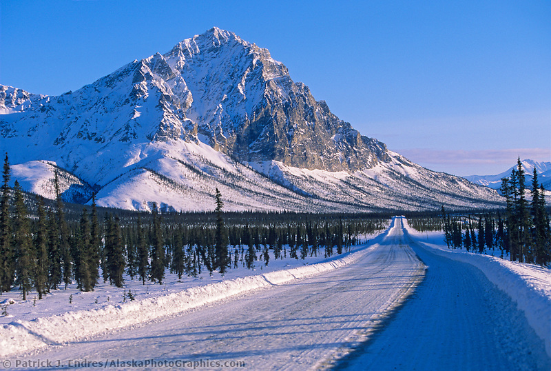 Afternoon light falls on the rugged face of Mount Dillon, situated adjacent to the snow covered James Dalton Highway, Brooks range, Alaska