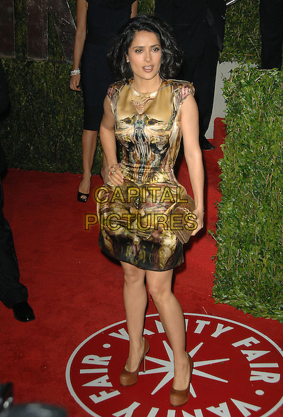 SALMA HAYEK.The 2010 Vanity Fair Oscar Party held at The Sunset Tower Hotel in West Hollywood, California, USA..March 7th, 2010.oscars full length cinched waist clutch bag brown gold beige silk satin sleeveless pattern print couture hand on hip.CAP/RKE/DVS.©DVS/RockinExposures/Capital Pictures.