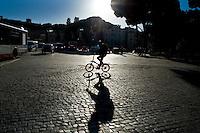 Un ciclista percorre un tratto di strada pavimentato con i classici sampietrini, in Piazza Venezia