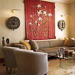 Neutral sitting room with tub armchairs sofa embroidered fabric wall hanging and exotic art pieces.