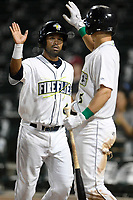 Second baseman Giovanny Alfonzo (6) of the Columbia Fireflies is greeted by Matt Winaker (5) after scoring a run during a game against the Charleston RiverDogs on Tuesday, August 28, 2018, at Spirit Communications Park in Columbia, South Carolina. Columbia won, 11-2. (Tom Priddy/Four Seam Images)