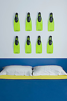 A row of acid yellow flippers has been hung on the wall above the bed as a quirky artwork