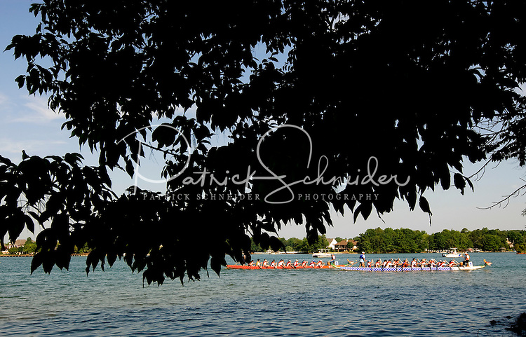 Riders paddle through the water during the Charlotte Dragonboat Association racing on Lake Norman in NC.