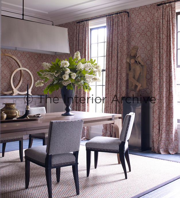 The walls of the dining room are lined with a subtle take on a traditional damask which compliments the carved statue of a Hindu goddess and an abstract circular wood sculpture