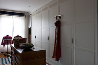 Cupboards line one wall of the bedroom which becomes a dressing area