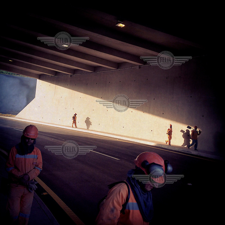 Workers walk through a tunnel which is part of the Ruta Viva (Living Road), a six-lane highway that connects the city and the airport.