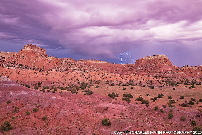 The red sandstone cliffs of Kitchen Mesa at Ghost Ranch become even more dramatic during a stormy moment at at sunset when bolts of lightning appear on the horizon.