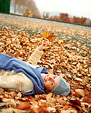 USA, California, portrait of happy young woman lying on autumn leaves