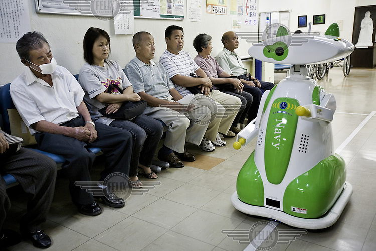 A robot  manufactured by Tsmuk Co. LTD. escorts patients to a lift in the Aidu Chuo Hospital. Robots are employed for simple tasks to ease the staff's workload.