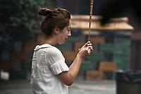 En face de la statue de bouddha Maitreya, le populaire bouddha du futur, une jeune chinoise adresse sa supplique en effectuant une offrande d'encens.