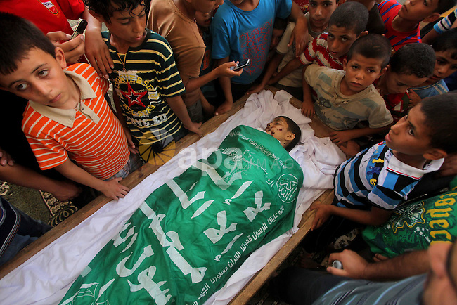 friends of 14-year old Palestinian Moamen al-Adam, who was killed in an Israeli air strike the day before, bids farewell to him during his funeral procession in Gaza city on June 21, 2012. The latest attacks follow three days of violence in which eight Palestinians were killed in Israeli air strikes while militants fired scores of rockets at the Jewish state, one of which slammed into a border police outpost, wounding four. Photo by Ashraf Amra