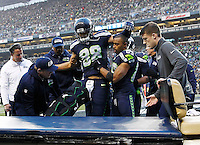 Jimmy Graham #88 of the Seattle Seahawks is helped to the cart by teammate Doug Baldwin #89 after injuring his knee on an attempted pass in the end zone against the Pittsburgh Steelers in the second half during the game at CenturyLink Field on November 29, 2015 in Seattle, Washington. (Photo by Jared Wickerham/DKPittsburghSports)