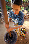 """Manggari woman pounding coffee to release the """"bean"""" from the fruit"""