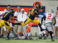 Darius Powe of California leaps over Ohio State defenders during the game at Memorial Stadium in Berkeley, California on September 14th, 2013.  Ohio State defeated California, 52-34.