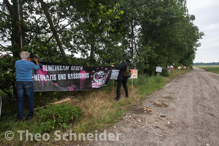 Nazigegner befestigen Transparente am Feldweg zum Hof Nahtz, auf dem die Sonnenwendfeier stattfindet. // Protest gegen Sonnenwendfeier auf Hof Nahtz in Eschede (Niedersachsen).