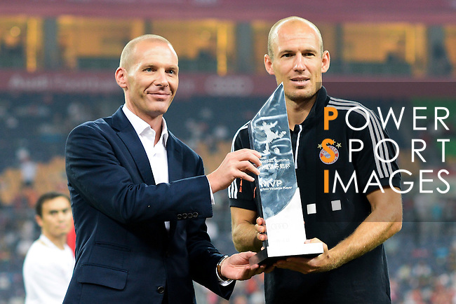 GUANGZHOU, GUANGDONG - JULY 26:  Arjen Robben (R) of Bayern Munich receives the MVP trophy from Dominique Boesch, Chief of the Audi sales division at FAW Wolkswagen, at the end of a friendly match against VfL Wolfsburg as part of the Audi Football Summit 2012 on July 26, 2012 at the Guangdong Olympic Sports Center in Guangzhou, China. Photo by Victor Fraile / The Power of Sport Images