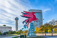 This cityscape image of Dallas with the orginal Red Flying Neon Pegasus Horse sitting on top of an oil derrick which rotates for different views is now located at the Omni Hotel in downtown Dallas. In this image you can see the Reunion Tower and the Omni Hotel with the Red neon Pegasus sitting atop of an oil derick and rotating around so it can be viewed from any angle. This neon Pegasus had sat on top of the Magnolia building since the 1934 which was 29 floors high building and it had been like a beacon for all who lived in and travel to Dallas.  The red pegasus was used as a symbol for the Magnolia Oil Company for many years till it became the Mobil Oil comapny where it continue to be used for many more years.  In the mean time this flying pegasus sitting a top of the Magnolia building has become an iconic landmark for the city for many years.  In 1999 the orginal pegasus for taken down from the top of Magnolia where it had sat since 1934 due rust,corrosion and age which regured it to come down. It was replace with a new pegasus.  Many in Dallas wanted to know what happen to the orginal Pegasus and began a search by a man name Jeremy McKain after a conversation with  82 year old June Mattingly who explain the importance of the flying horse symbol he was even more sure they needed to find it and see if it could be restored.  McKain was recruited by Matthew Southwest to help provide the art for Omni Hotel and after speaking with the vise president Jeff West of the company a common bond was form to find the Pegasus.  McKane with the help of Jeff continue to talk to people and over a period of time the orginal flying pegasus was found in a city storage shed near White Rock.  Jeff West got the finacing from his company to restore the project so with McKane and a group of artist and experts were able to bring this landmark back to life on the lawn of the Omni Hotel for all to enjoy again.