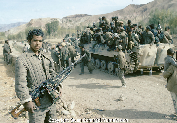 A young Mujahedin taking the pose in the middle of a chaos of war.Army force of warlord Ahmad Shah Massoud (Jamiat-e-Islami and mercenary of Arakat-e-Islami) running away from the Karim Kalili Hezb-e-Wahdat Islami Hazara Mujahedins force in the Bamiyan valley in 1995.Mass exodus and hundreds of causality on the local population escaping the fight in Bamiyan.