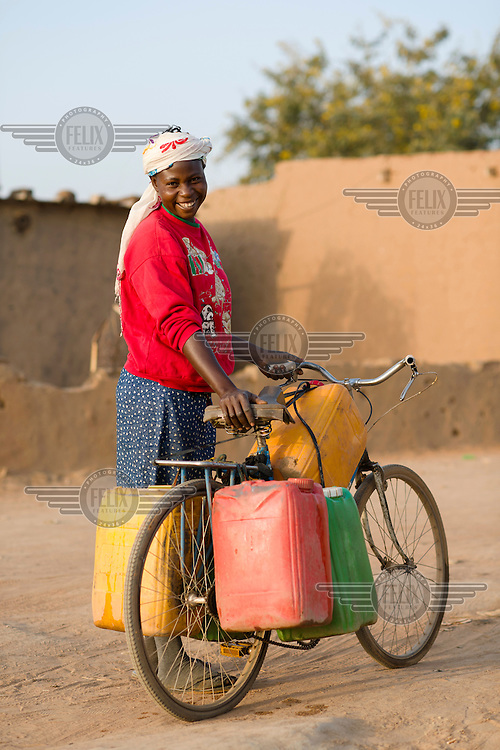Mariam Ouedraogo (37) wheeling jerry cans of water from the nearest pump to her home in the informal settlement of Zongo. Fetching water for the household is a time-consuming and laborious task which falls primarily on the shoulders of women and girls.