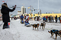 Sigrid Ekran waves to a trail guard on 4th avenue at the Ceremonial Start of the 2016 Iditarod in Anchorage, Alaska.  March 05, 2016