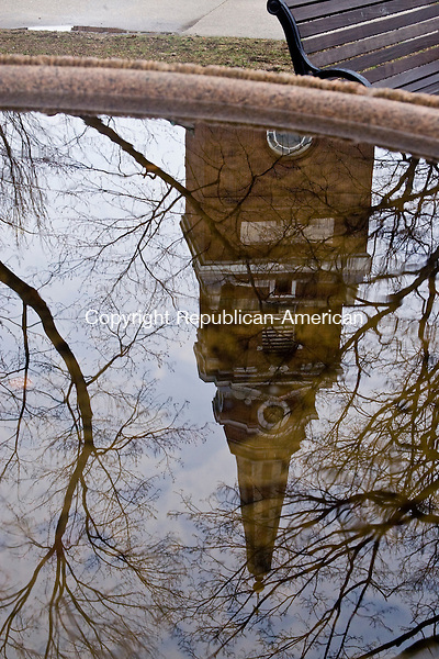 NAUGATUCK, CT - 22 MARCH 2010 -032110JT02-<br /> A reflection of the Naugatuck Congregational Church can be seen in a pool of rainwater collected at the fountain on the Naugatuck Green on Monday.<br /> Josalee Thrift Republican-American