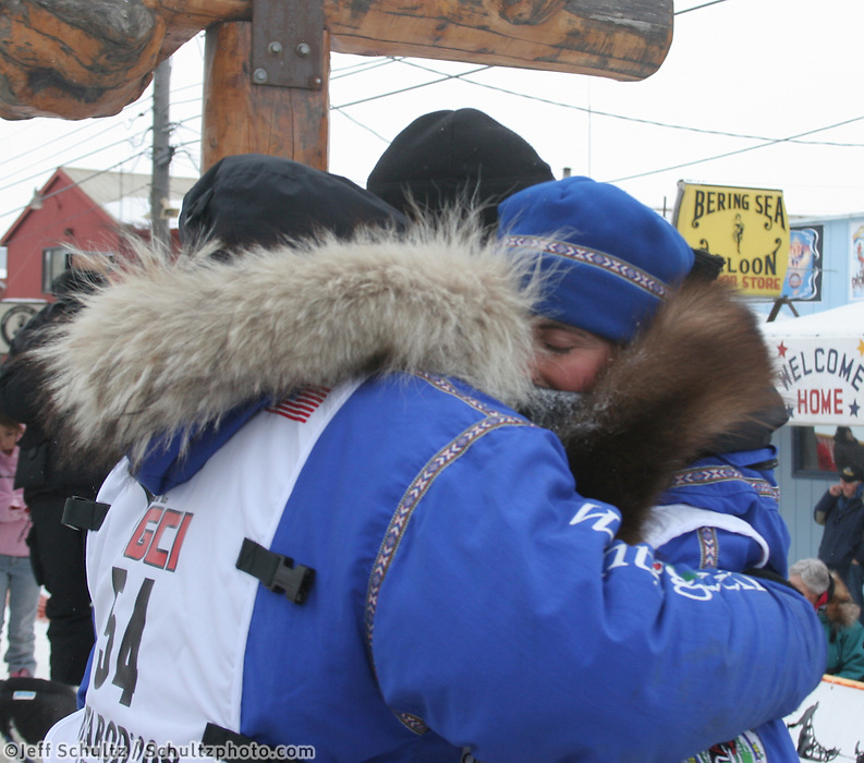 Blake and Jennifer Freking hug under the burled arch finish line in Nome, Alaska, after finishing the Iditarod together. Photo by Jon Little.