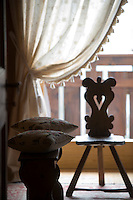 A 19th century wooden chair is silhouetted against the window