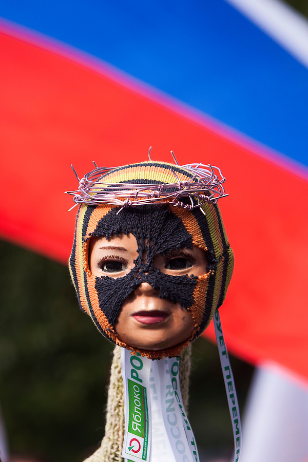 Moscow, Russia, 19/08/2012..A doll dressed as a member of Pussy Riot with a crown of barbed wire in front of a Russian flag  at a Russian opposition rally. Several hundred opposition demonstrators gathered near the Russian government White House to mark the 21st anniversary of the attempted coup in 1991 by Communist hardliners that led to the eventual break-up of the Soviet Union.