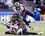 Seattle Seahawks running back Robert Turbin (22) goes airborne after getting tackled by St. Louis Rams cornerback Marcus Robinson (47) and safety Rodney McLeod (23) after running for 14 yards and a first down during the second quarter  at CenturyLink Field in Seattle, Washington on December 28, 2014. The Seahawks officially wrapped up the No. 1 seed in the NFC playoffs shortly after beating the Rams, 20-6. Despite the Cowboys and Packers also winning to finish 12-4, the Seahawks (12-4) won the multi-team tiebreaker and earned home-field advantage throughout the playoffs for the second consecutive season.  ©2014. Jim Bryant Photo. All Rights Reserved.