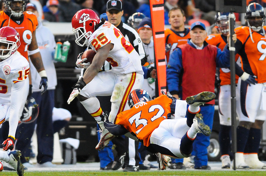 14 NOVEMBER 2010:  Chiefs running back Jamaal Charles leaps to avoid a tackle by Broncos cornerback Perrish Cox  during a regular season National Football League game between the Kansas City Chiefs and the Denver Broncos at Invesco Field at Mile High in Denver, Colorado. The Broncos beat the Chiefs 49-29.