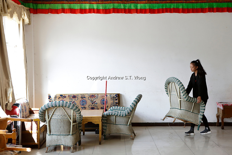Lhasa, Tibet, China - A Tibetan teacher  cleans up and arrange seats at a town hall in Lhasa in preparation of a weekend charity tutoring for poor youths, September 2018.