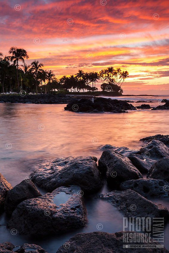 A fiery sunset's colors are reflected in the waters at Pauoa Bay, Big Island.